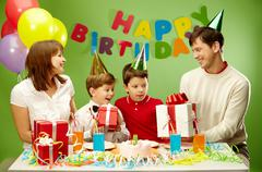 Portrait of boy holding his present with happy parents and brother near by Stock Photos