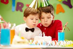 Portrait of happy boys on birthday party blowing at candles on cake Stock Photos