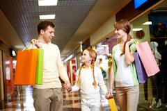 image of family carrying bags and interacting in the mall - stock photo