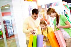 image of parents showing their daughter what they bought in the mall - stock photo