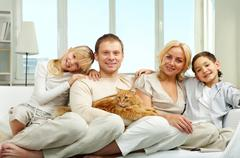 Stock Photo of a young family with son and daughter sitting on sofa, looking at camera and smil