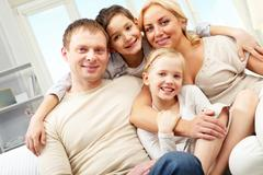 A family of four embracing and smiling at home Stock Photos