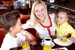 Portrait of happy woman with her two cute children in cafe Stock Photos
