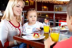 portrait of happy family having lunch in cafe - stock photo