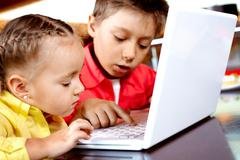Portrait of cute children typing on laptop Stock Photos
