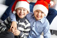 Two lads in santa hats smiling and looking at camera Stock Photos