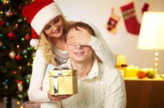 portrait of happy woman closing male's eyes by her hands while holding giftbox i - stock photo