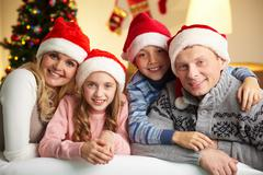 portrait of four happy family members in santa caps looking at camera with smile - stock photo