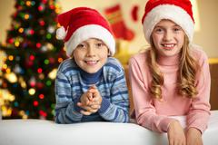 adorable siblings in santa hats smiling and looking at camera - stock photo