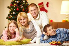 portrait of four happy family members looking at camera with smiles - stock photo