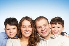 a young family of four looking at camera and smiling - stock photo
