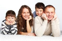 A young family of father, mother and two kids posing in front of camera Stock Photos
