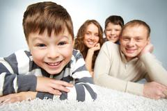 a young family of father, mother and lad with happy boy in front looking at came - stock photo