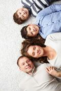 a young family lying on the floor and looking at camera - stock photo