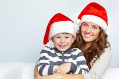 mother and son in santa hats smiling and looking at camera - stock photo