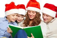 portrait of four happy family members in santa caps reading book - stock photo