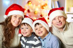 portrait of four happy family members in santa caps looking at camera - stock photo