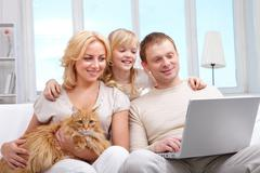 a family of three with cat sitting on sofa and looking at laptop screen - stock photo