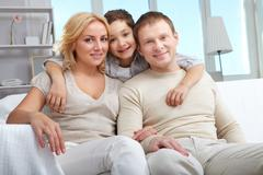 Stock Photo of a family with son embracing, looking at camera and smiling