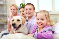 A happy family of four with a dog sitting on sofa, the focus is on the daughter Stock Photos