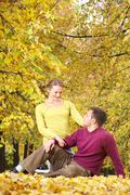 young couple sitting together on leaves in autumn park - stock photo