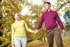 Portrait of couple walking in autumn holding hands Stock Photos