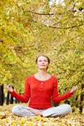 Portrait of young woman meditating outdoors in autumn Stock Photos