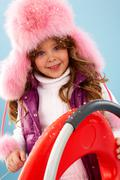 happy girl in furry hat looking at camera - stock photo