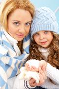 portrait of mother and her daughter in winter clothes looking at camera - stock photo