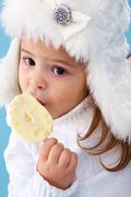 Little girl in white furry hat eating delicious ice-cream Stock Photos