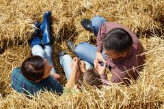 above angle of family of three having rest in countryside - stock photo