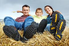 happy family of three spending time in countryside - stock photo