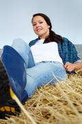 Happy woman lying on hay and looking at camera Stock Photos