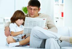 photo of cute boy and his father reading newspaper together at home - stock photo