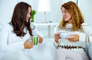 Photo of pretty woman and her teenage daughter having tea at home Stock Photos