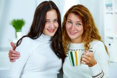 photo of pretty woman and her teenage daughter looking at camera - stock photo