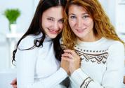 Photo of attractive woman and her teenage daughter looking at camera Stock Photos