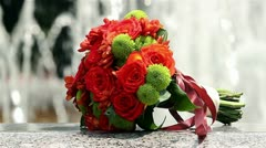Bouquet of red and green flowers outside, Bride's bouquet near the fountain - stock footage