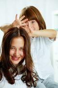 Photo of attractive teenager and her little brother having fun Stock Photos