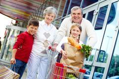portrait of happy grandparents and grandchildren near supermarket - stock photo
