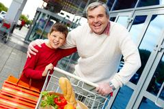 Portrait of grandfather and grandson with goods near supermarket Stock Photos