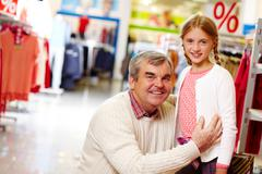 portrait of grandfather and granddaughter in clothing department - stock photo