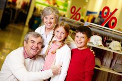 Portrait of happy grandparents and grandchildren in clothing department Stock Photos