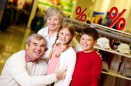 Portrait of happy grandparents and grandchildren in clothing department Stock Photos
