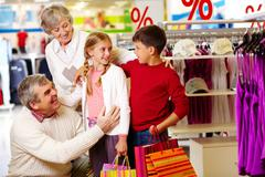 portrait of happy grandparents and grandchildren in department store - stock photo