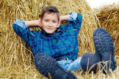 happy lad lying on hay in countryside - stock photo