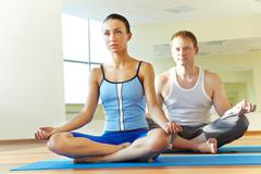 Photo of meditating girl and young man in pose of lotus Stock Photos