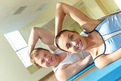 portrait of young sporty couple doing exercise on floor - stock photo