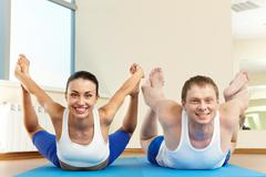portrait of young sporty couple doing physical exercise on floor - stock photo