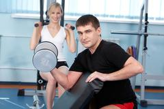 a man lifting a barbell with a woman training on exercise machine in the backgro - stock photo